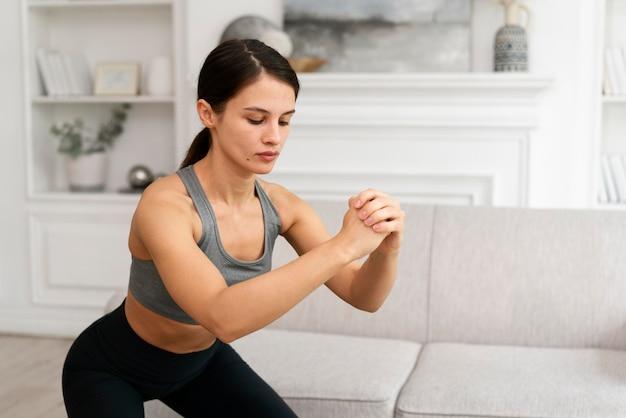 Mulher jovem em roupas esportivas se exercitando em casa