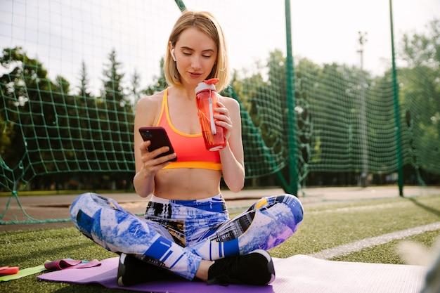Mulher jovem em roupas esportivas se senta no tapete, bebe água e usa um smartphone.