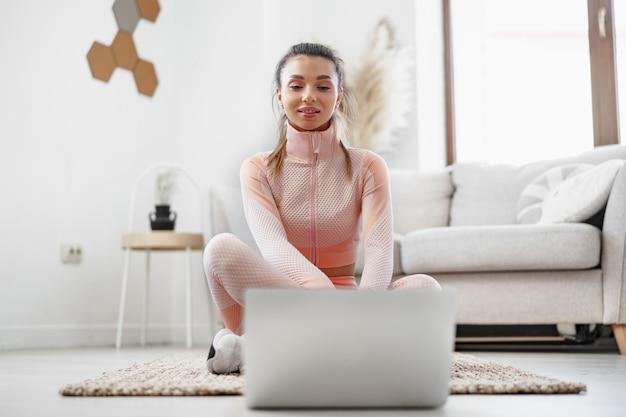Mulher jovem em roupas esportivas usando laptop para assistir a tutoriais em vídeo de exercícios em casa
