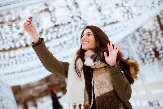 Mulher jovem, em, roupas inverno, levando, selfie, por, smartphone, ao ar livre
