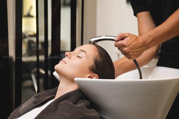 Mulher jovem em salão de cabeleireiro durante lavagem de cabelo após corte de cabelo Foto Premium