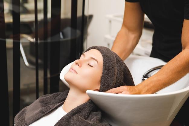 Mulher jovem em salão de cabeleireiro durante lavagem de cabelo após corte de cabelo