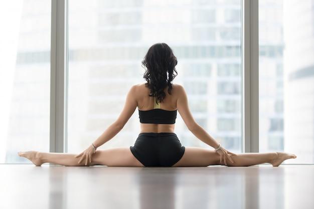 Mulher jovem, em, samakonasana, pose, contra, janela chão, vista traseira