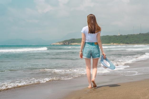 Mulher jovem em shorts jeans e camiseta branca, caminhando ao longo da costa do mediterrâneo