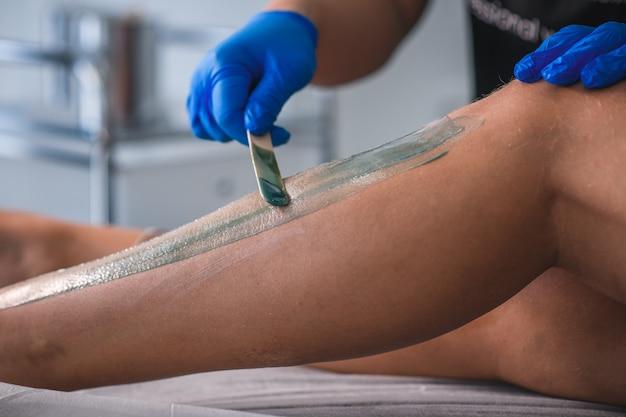 Mulher jovem em spa fazendo depilação com cera nas pernas
