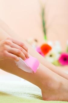 Mulher jovem em spa recebendo creme nas pernas para depilação