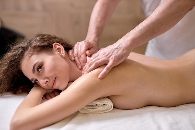 Mulher jovem em spa resort recebendo massagem nos músculos do pescoço e ombros