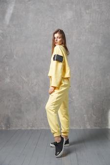 Mulher jovem em sportswear amarelo, calças e moletom. conceito de roupa de esporte na moda, foto de dentro de casa. copie o espaço.