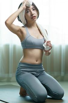 Mulher jovem em sportswear cinza com toalha, pausa após o treino
