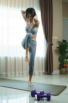 Mulher jovem em sportswear cinza exercer em casa, fazendo flexões de bicicleta em pé