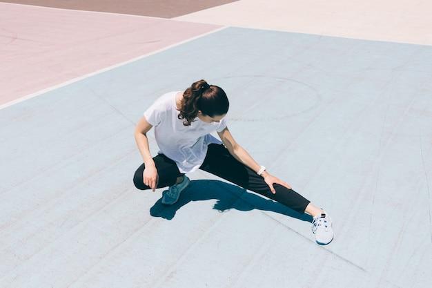 Mulher jovem, em, sportswear, fazendo, esticar, perna, ligado, a, pátio recreio