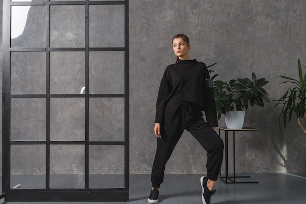 Mulher jovem em sportswear preto, calças e moletom. conceito de roupa de esporte na moda, foto de dentro de casa. copie o espaço. o conceito de esportes, estilo de vida saudável, fitness, alongamento