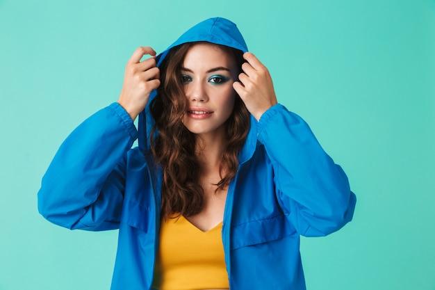 Mulher jovem em streetwear, colocando o capuz da capa de chuva ou jaqueta