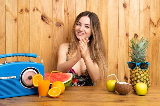 Mulher jovem, em, swimsuit, com, lotes, de, frutas, aplaudindo