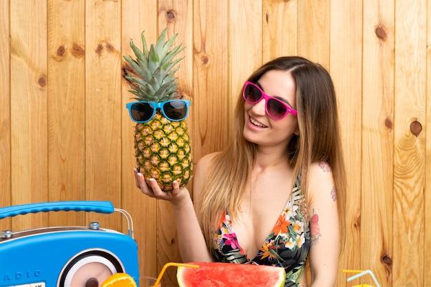 Mulher jovem, em, swimsuit, segurando, um, abacaxi, com, óculos de sol