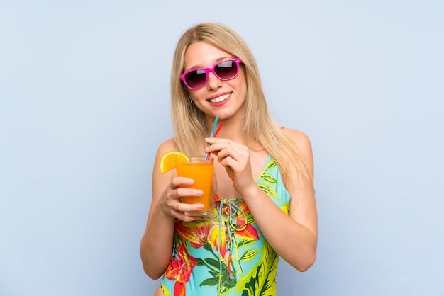 Mulher jovem, em, swimsuit, sobre, azul, com, um, coquetel