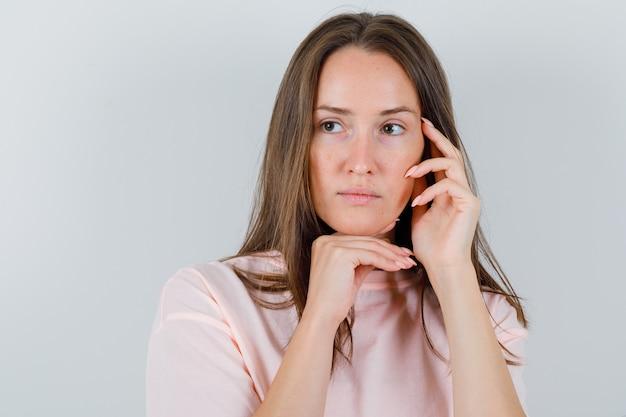 Mulher jovem em t-shirt, apoiando o queixo na mão enquanto toca o rosto e parece pensativa, vista frontal.
