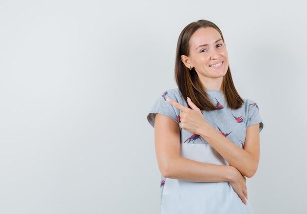 Mulher jovem em t-shirt apontando para longe e olhando confiante, vista frontal.