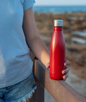 Mulher jovem em t-shirt azul claro segurando uma garrafa de água reutilizável vermelha na mão close-up, tiro recortado. maquete de garrafa e camiseta