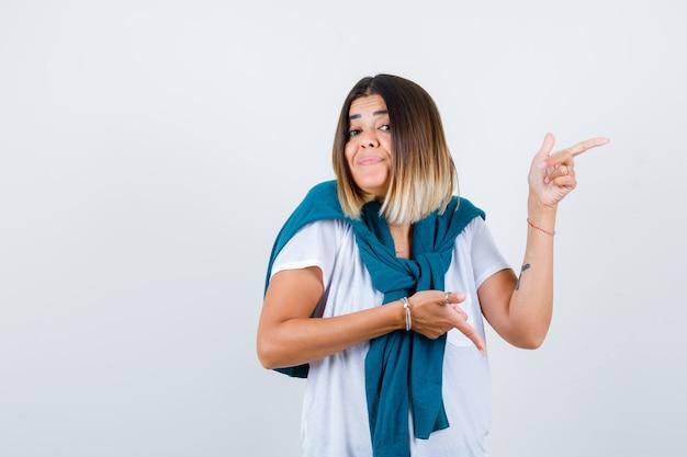 Mulher jovem em t-shirt branca apontando para o lado e para baixo e olhando pensativa, vista frontal.