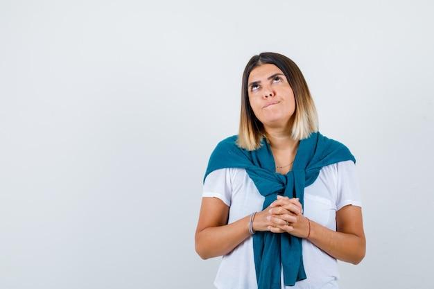 Mulher jovem em t-shirt branca com as mãos na frente dela, olhando para cima e parecendo perplexo, vista frontal.