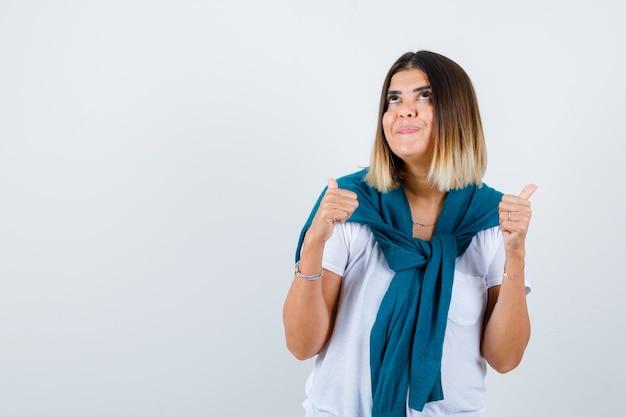 Mulher jovem em t-shirt branca, mostrando os polegares para cima e olhando atraente vista frontal.