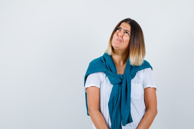 Mulher jovem em t-shirt branca, torcendo a boca para o lado e olhando melancólica, vista frontal.
