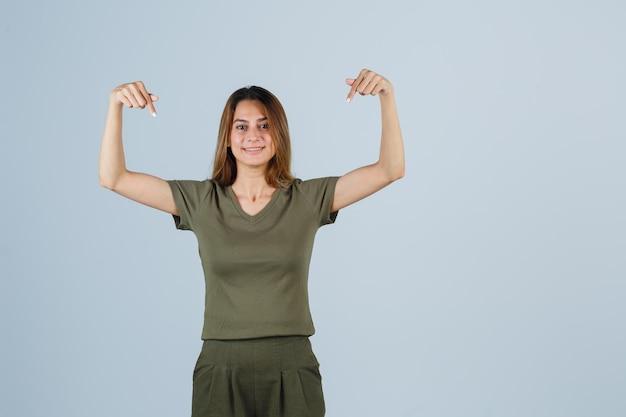 Mulher jovem em t-shirt, calças apontando para baixo e parecendo feliz, vista frontal.