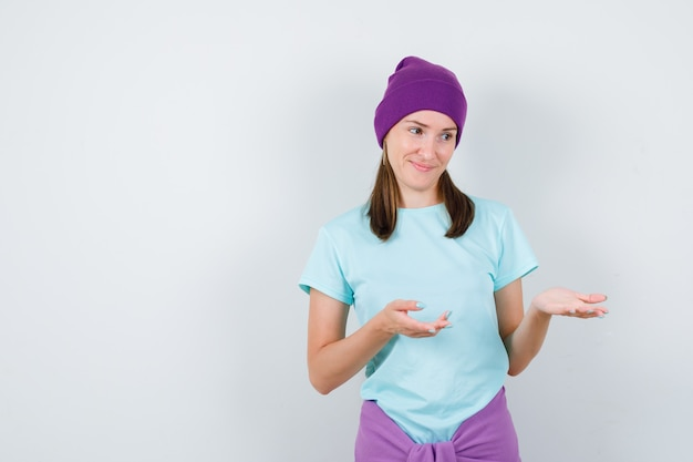 Mulher jovem em t-shirt, gorro fingindo mostrar algo e olhando alegre, vista frontal.