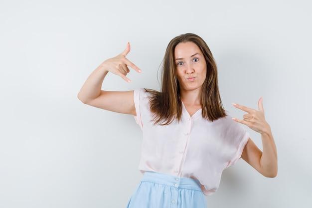 Mulher jovem em t-shirt, saia, mostrando o gesto 'eu te amo', vista frontal.