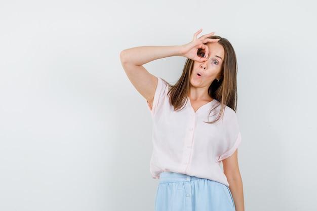 Mulher jovem em t-shirt, saia, mostrando o gesto ok no olho e olhando engraçado, vista frontal.