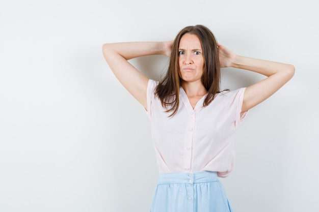Mulher jovem em t-shirt, saia segurando as mãos atrás da cabeça e olhando com raiva, vista frontal.