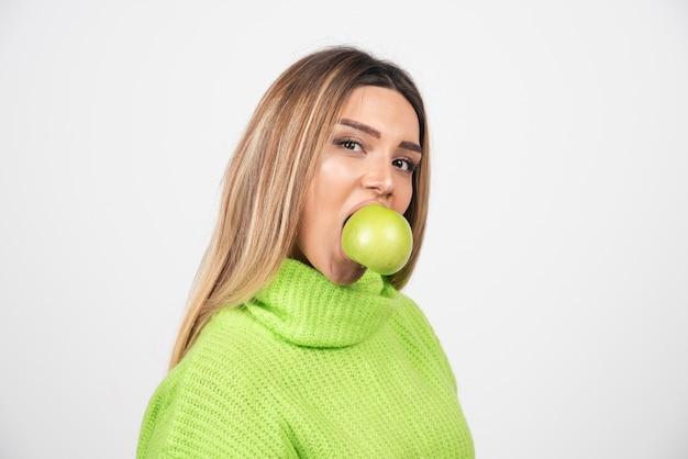Mulher jovem em t-shirt verde comendo uma maçã.