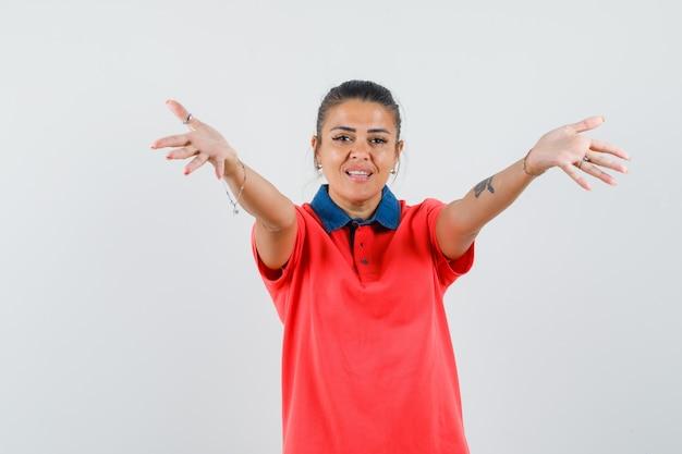 Mulher jovem em t-shirt vermelha, esticando as mãos como um convite para entrar e olhar amável, vista frontal.