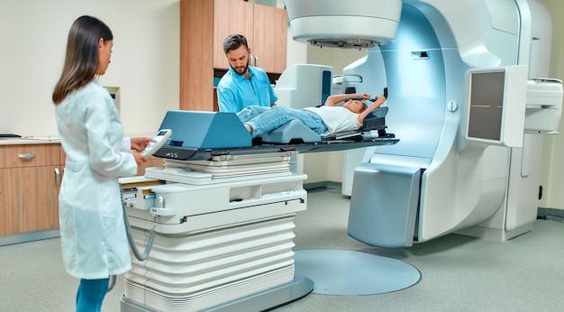 Mulher jovem em terapia de radiação para câncer sob a supervisão de médicos