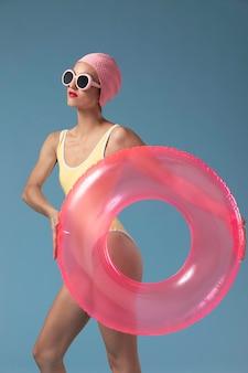 Mulher jovem em traje de banho com uma argola de natação