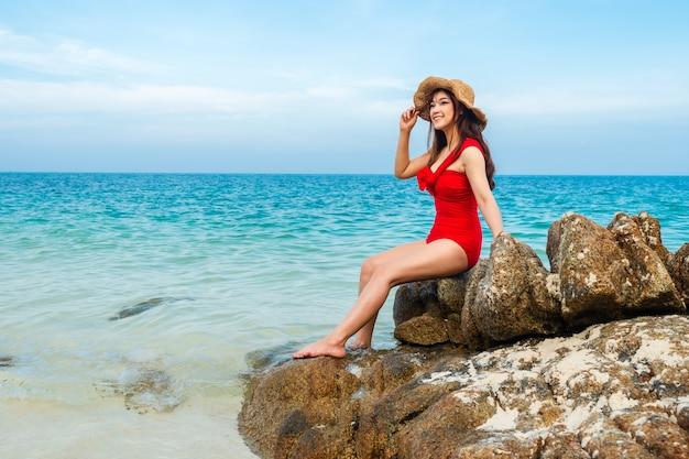 Mulher jovem em traje de banho sentada na praia de pedra com o mar na ilha de koh munnork, rayong, tailândia