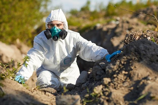 Mulher jovem em traje de proteção e máscara trabalhando como ecologista. ela examinando a natureza