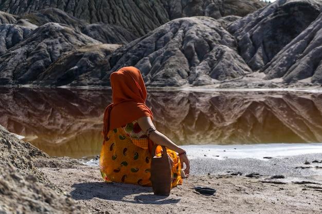 Mulher jovem em trajes étnicos sentada com uma jarra na margem de um lago em um vale deserto