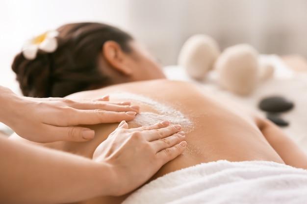 Mulher jovem em tratamento com esfoliação corporal em salão de spa