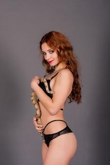 Mulher jovem em um biquíni preto posando com python contra um fundo abstrato