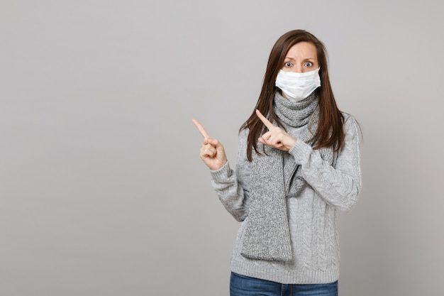 Mulher jovem em um cachecol de suéter cinza com máscara facial estéril, apontando os dedos indicadores de lado, isolados em fundo cinza. estilo de vida saudável doente doente doença tratamento conceito de estação fria. simule o espaço da cópia.