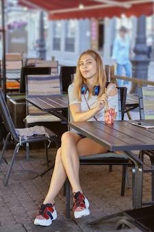 Mulher jovem em um café de rua.