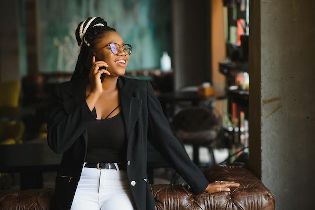 Mulher jovem em um café falando ao telefone