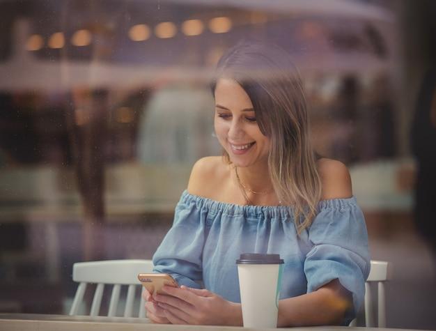 Mulher jovem em um café tomando café e usando o telefone celular enquanto está sentada perto da janela