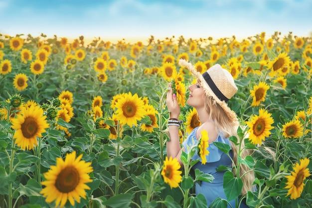 Mulher jovem em um campo de girassóis florescendo