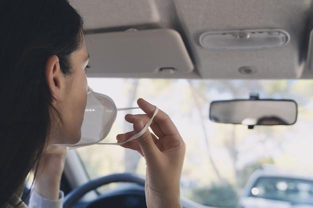 Mulher jovem em um carro usando uma máscara protetora durante a pandemia de covid-19