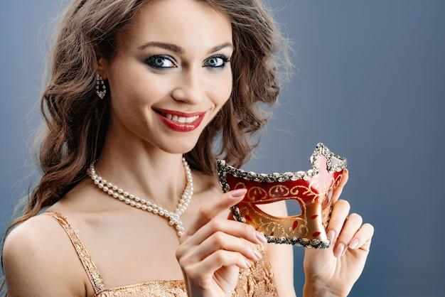 Mulher jovem, em, um, colar pérola, sorrisos, segura, um, máscara carnaval, em, dela, mão, close-up
