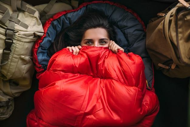 Mulher jovem em um confortável saco de dormir em uma barraca, vista de cima. um turista em um saco de dormir. um viajante embrulhado em um saco de dormir vermelho. viagem, conceito de acampamento, aventura. viajando com uma barraca