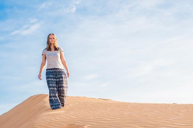 Mulher jovem em um deserto de areia radiante ao pôr do sol ou amanhecer